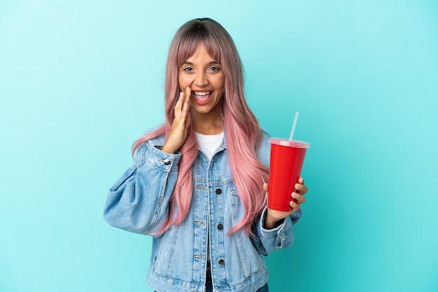 푸른 배경에 격리된 신선한 음료를 마시는 젊은 혼혈 여성이 입을 크게 벌리고 소리를 질러