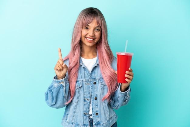 파란색 배경에 격리된 신선한 음료를 마시고 있는 젊은 혼혈 여성이 최고라는 표시로 손가락을 들고 들어올립니다