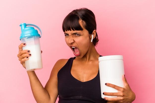 ピンクの背景に分離されたプロテインシェイクを飲む若い混血の女性
