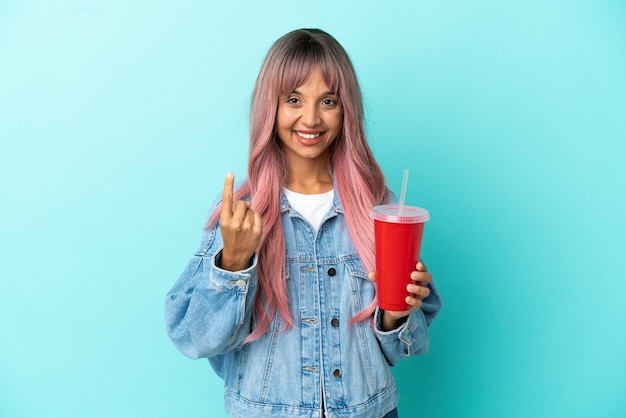 Young mixed race woman drinking a fresh drink isolated on blue background doing coming gesture