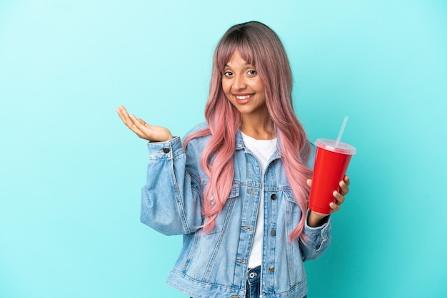Young mixed race woman drinking a fresh drink isolated on blue background extending hands to the side for inviting to come