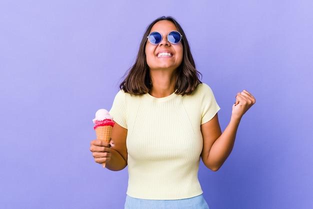 승리, 열정과 열정, 행복한 표정을 축하하는 아이스크림을 먹는 젊은 혼합 된 인종 여자.