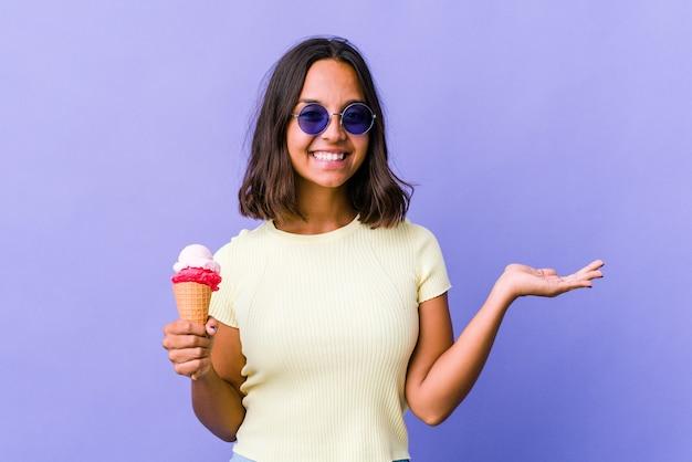 手のひらにコピースペースを示し、腰に別の手を握ってアイスクリームを食べる若い混血の女性。