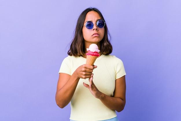 タイムアウトジェスチャーを示すアイスクリームを食べる若い混血の女性。