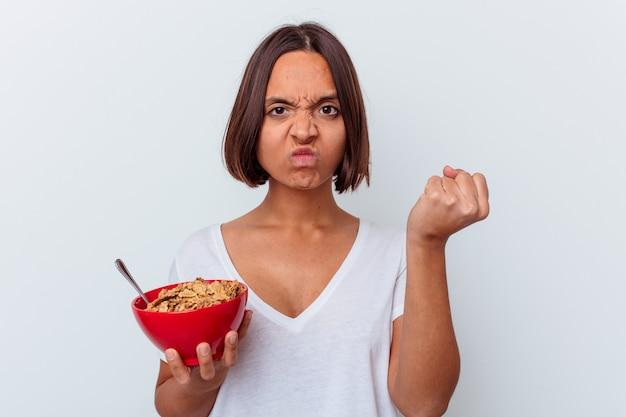 카메라, 공격적인 표정에 주먹을 보여주는 흰 벽에 고립 된 곡물을 먹는 젊은 혼합 된 인종 여자.