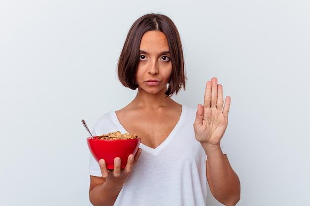 Молодая женщина смешанной расы ест хлопья, изолированные на белой стене, стоя с протянутой рукой, показывая знак остановки, предотвращая вас.
