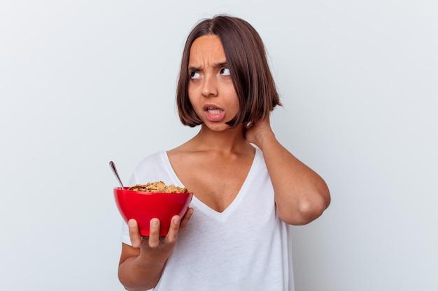 젊은 혼합 된 인종 여자 머리 뒤로 만지고, 생각 하 고 선택을하는 흰 벽에 고립 된 곡물을 먹고.