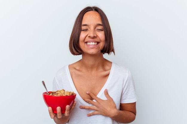 Young mixed race woman eating cereals isolated on white background laughing and having fun.