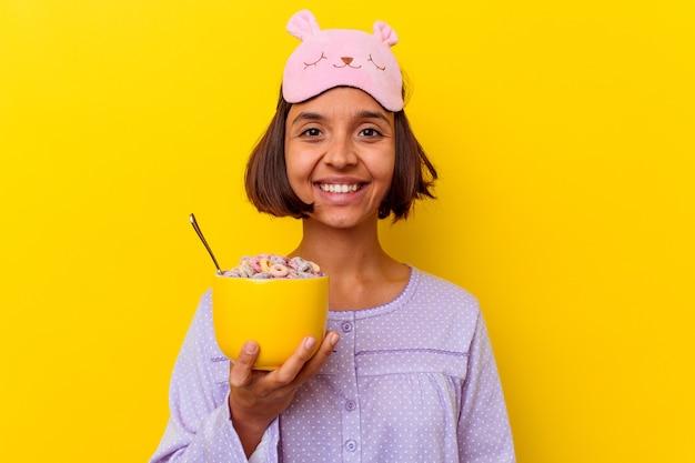 幸せ、笑顔、陽気な黄色の背景に分離されたパジャマを着てシリアルを食べる若い混血の女性。