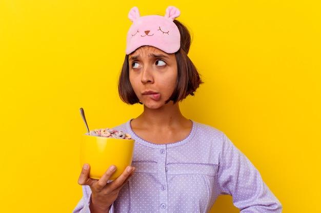 Молодая женщина смешанной расы ест хлопья в пижаме, изолированной на желтой стене, смущена, чувствует себя сомнительной и неуверенной.