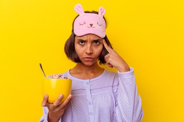 생각, 작업에 초점을 맞춘 손가락으로 사원을 가리키는 노란색 벽에 고립 된 pijama를 입고 시리얼을 먹는 젊은 혼합 된 인종 여자.