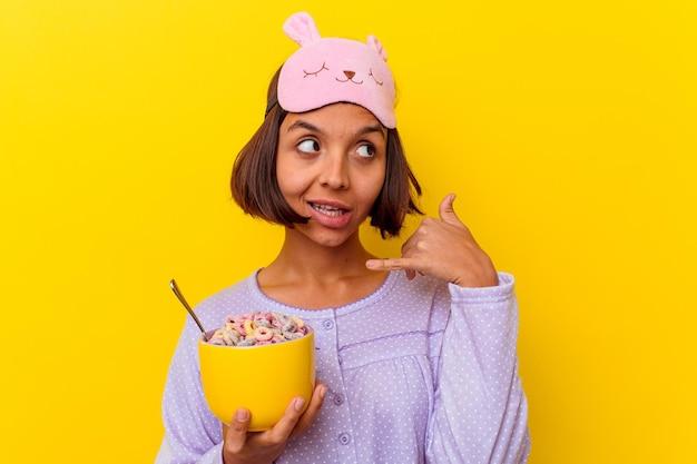指で携帯電話の呼び出しジェスチャーを示す黄色の壁に分離されたパジャマを着てシリアルを食べる若い混血の女性。