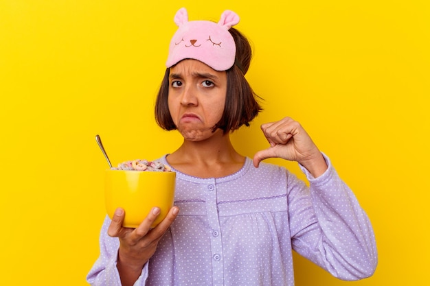 Young mixed race woman eating cereals wearing a pijama isolated on yellow wall feels proud and self confident, example to follow.