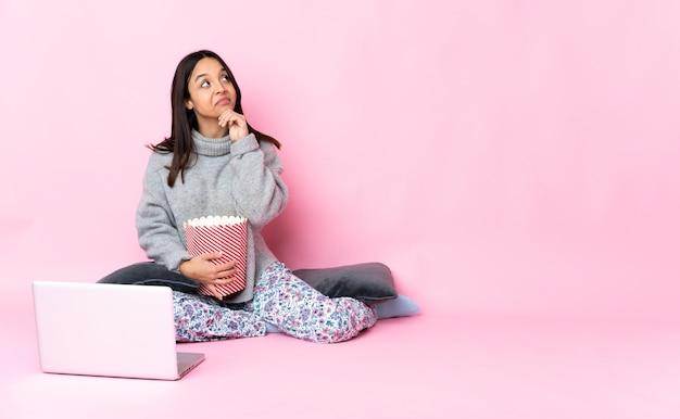 Молодая женщина смешанной расы ест попкорн во время просмотра фильма на ноутбуке и смотрит вверх