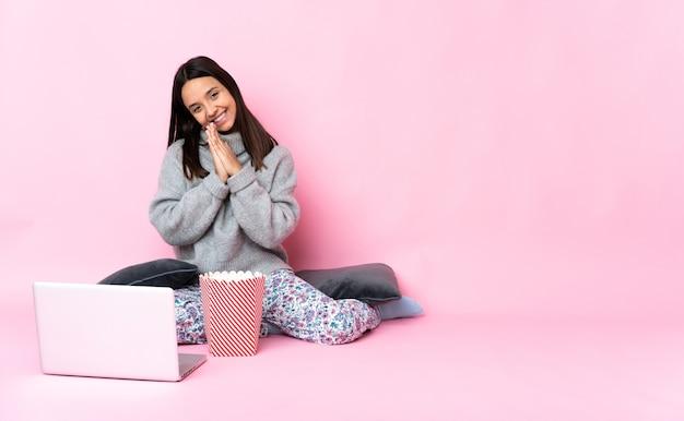 Молодая женщина смешанной расы ест попкорн во время просмотра фильма на ноутбуке держит ладонь вместе. человек о чем-то просит