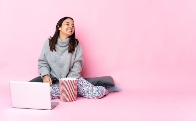 笑っているラップトップで映画を見ながらポップコーンを食べる若い混血の女性