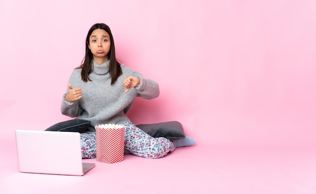 Молодая женщина смешанной расы ест попкорн во время просмотра фильма на ноутбуке, делая знак