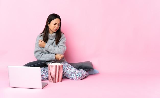 Молодая женщина смешанной расы ест попкорн во время просмотра фильма на ноутбуке с болью в локте