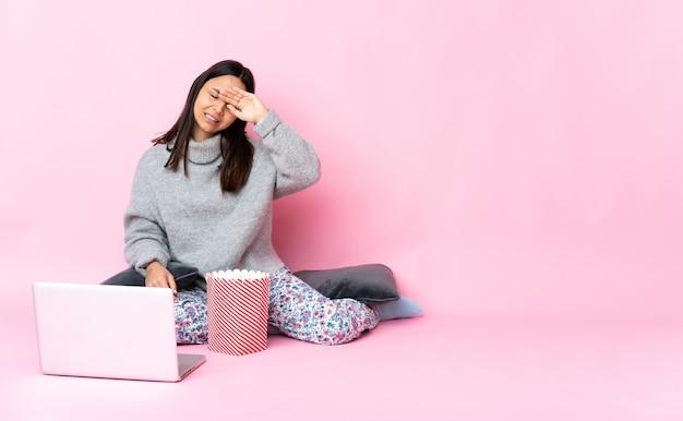 Молодая женщина смешанной расы ест попкорн во время просмотра фильма на ноутбуке с усталым и больным выражением лица