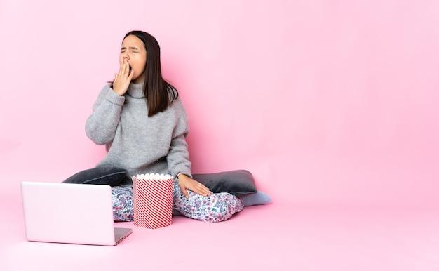 Молодая женщина смешанной расы ест попкорн во время просмотра фильма на ноутбуке, зевая и прикрывая широко открытый рот рукой