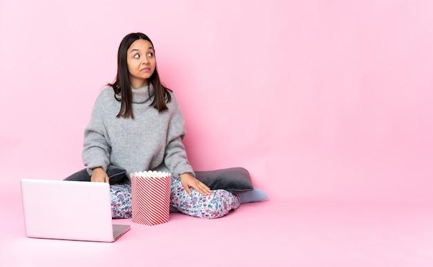 Молодая женщина смешанной расы ест попкорн во время просмотра фильма