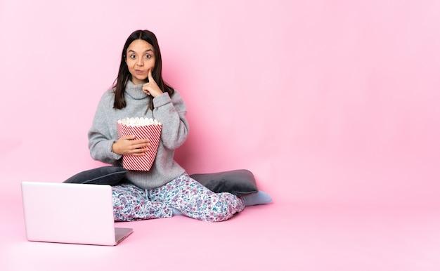 영화를 보면서 팝콘을 먹는 젊은 혼혈 여자