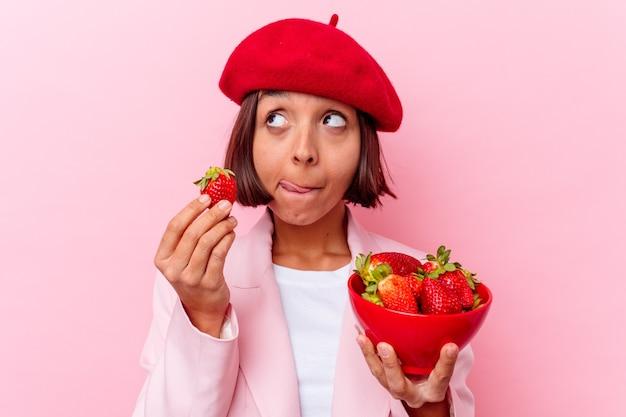 ピンクの背景に分離されたイチゴを食べる若い混血の女性