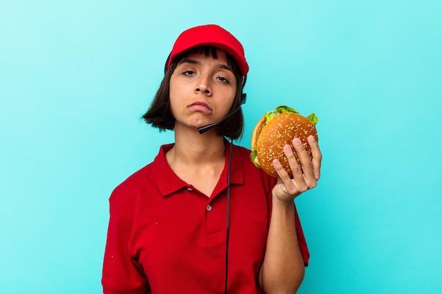 파란색 배경에 고립 된 햄버거를 들고 젊은 혼혈 여자 패스트 푸드 레스토랑 노동자
