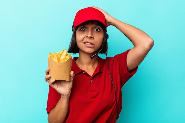 ショックを受けている青い背景に分離されたフライドポテトを保持している若い混血の女性ファーストフードレストランの労働者、彼女は重要な会議を思い出しました。