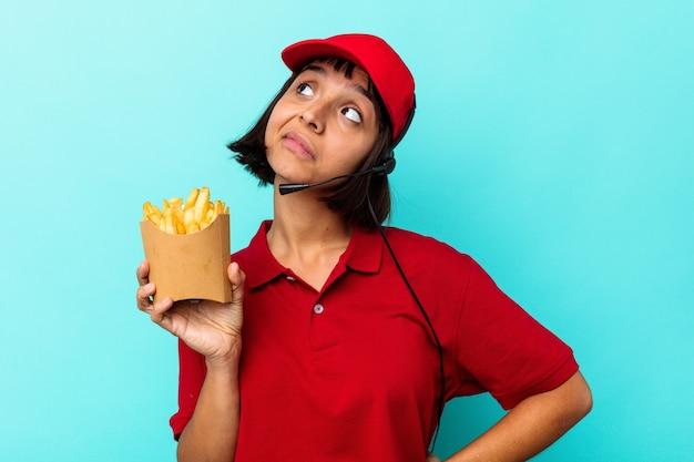 目標と目的を達成することを夢見て、青い背景に分離されたフライド ポテトを保持している若い混血女性ファーストフード レストランの労働者