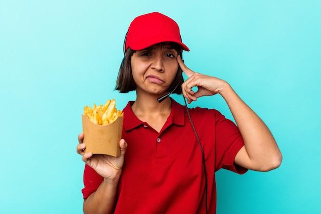 Молодой работник ресторана быстрого питания женщины смешанной расы, держащий картофель фри, изолированный на синем фоне, указывая храм пальцем, думая, сосредоточился на задаче.