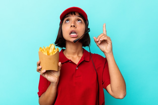 열린 된 입으로 거꾸로 가리키는 파란색 배경에 고립 된 감자 튀김을 들고 젊은 혼합 된 경주 여자 패스트 푸드 레스토랑 노동자.