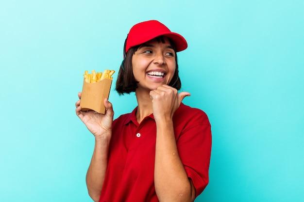 젊은 혼합 된 경주 여자 패스트 푸드 레스토랑 노동자 엄지 손가락으로 멀리, 웃 고 평온한 파란색 배경 포인트에 고립 된 감자 튀김을 들고.