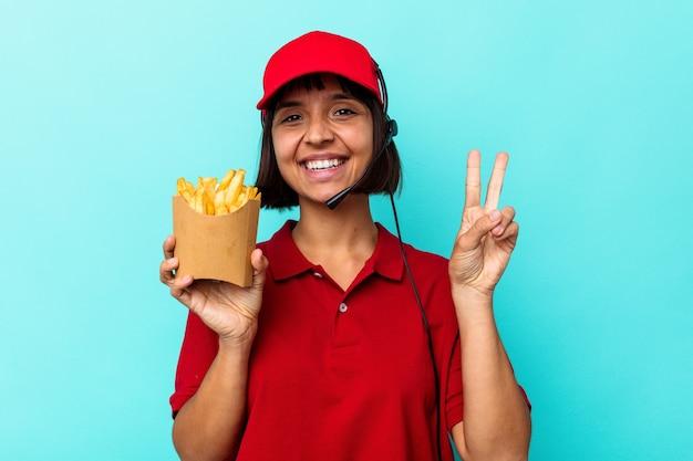 젊은 혼합 된 경주 여자 패스트 푸드 레스토랑 노동자 손가락으로 2 번을 보여주는 파란색 배경에 고립 된 감자 튀김을 들고.
