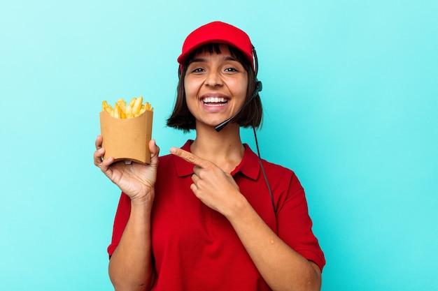 젊은 혼합 된 경주 여자 패스트 푸드 레스토랑 노동자 웃 고 옆으로 가리키는 파란색 배경에 고립 된 감자 튀김을 들고 빈 공간에서 뭔가 보여주는.