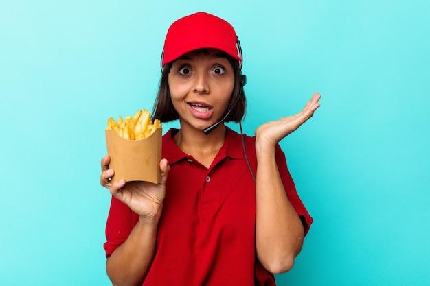 青の背景に分離されたフライド ポテトを保持している若い混血女性ファーストフード レストランの労働者は驚き、ショックを受けました。