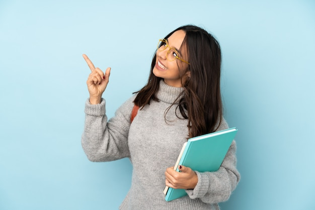 Young mixed race woman going to school on blue wall pointing with the index finger a great idea