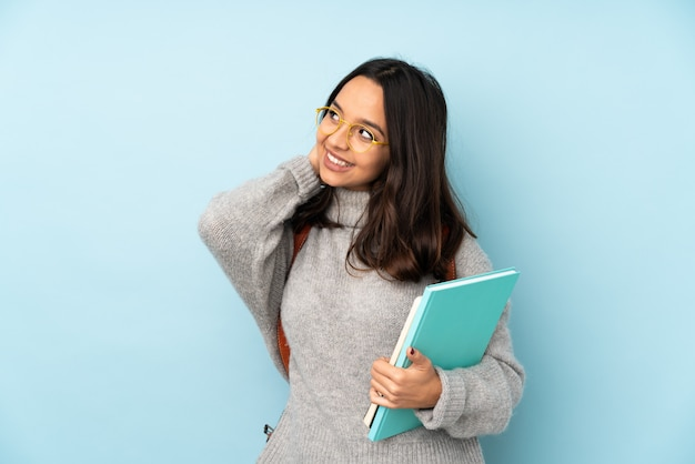 Young mixed race woman going to school on blue wall thinking an idea
