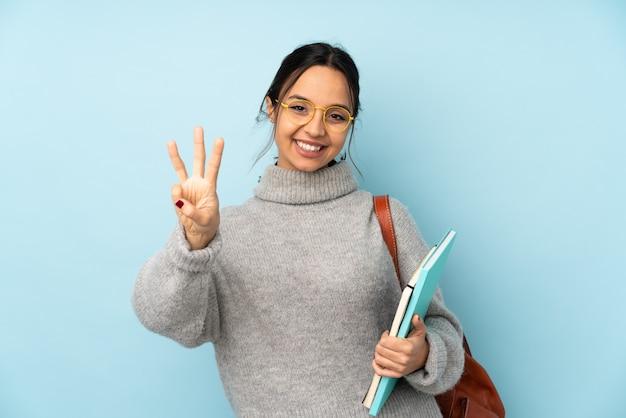 幸せな青い壁と指で3つを数える上に分離されて学校に行く若い混血女性