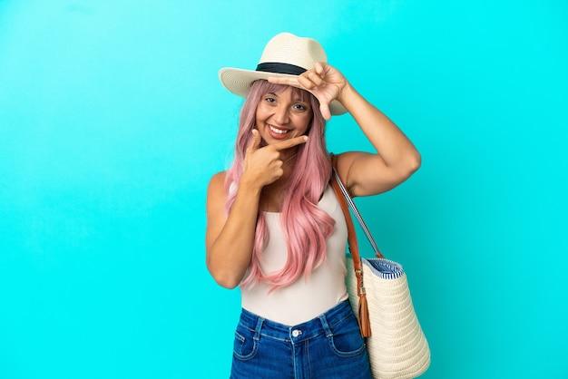 Молодая женщина смешанной расы, держащая пляжную сумку с памелой, изолированной на синем фоне, фокусируя лицо. обрамление символа
