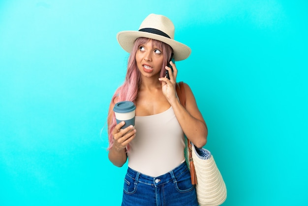 Молодая женщина смешанной расы, держащая пляжную сумку с памелой, изолированную на синем фоне, держит кофе на вынос и мобильный