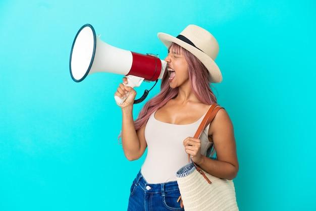 Молодая женщина смешанной расы держит пляжную сумку с памелой, изолированной на синем фоне, кричит в мегафон