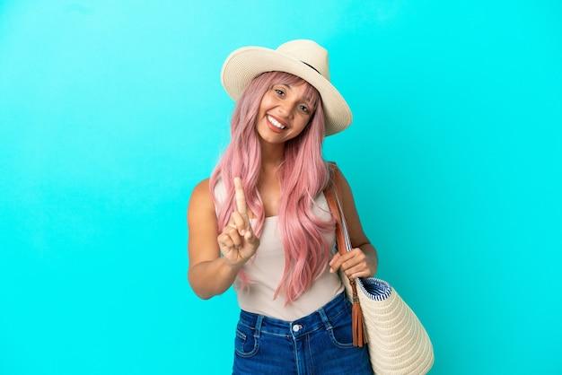 Молодая женщина смешанной расы держит пляжную сумку с памелой, изолированной на синем фоне, показывает и поднимает палец