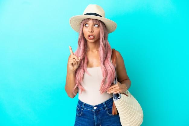 指を上に向けるアイデアを考えて青い背景で隔離のパメラとビーチバッグを保持している若い混血の女性