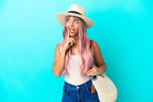 Молодая женщина смешанной расы, держащая пляжную сумку с памелой, изолирована на синем фоне, думая об идее, глядя вверх