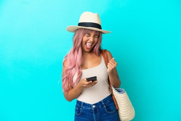 勝利の位置に電話で青い背景に分離されたパメラとビーチバッグを保持している若い混血の女性