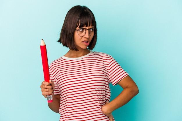 青い背景に分離された大きな鉛筆を持っている若い混血の女性は混乱し、疑わしく、不安を感じます。