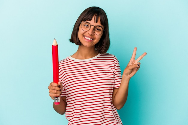 青い背景に分離された大きな鉛筆を持っている若い混血の女性は、指で平和のシンボルを喜んで気楽に示しています。