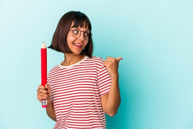 親指の指を離れて、笑いながらのんびりと青い背景のポイントに分離された大きな鉛筆を保持している若い混血の女性。