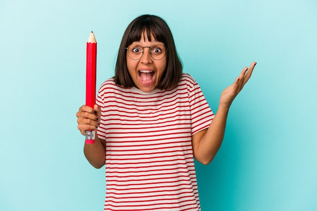 青い背景に分離された大きな鉛筆を持っている若い混血の女性は、嬉しい驚きを受け取り、興奮し、手を上げます。
